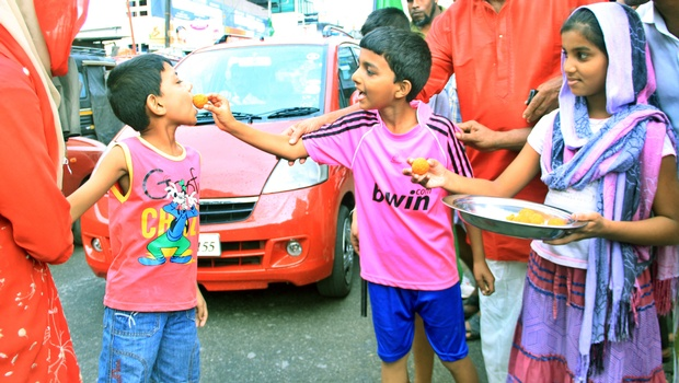 Distribute sweets to everybody in the bus stand
